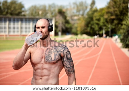 one young strong tattooed man shirtless barechestedness, bodybuilder, 30-35 years, drinking water from bottle. Outdoors, sports venue, running tracks (out of focus). upper body shot. #1181893516