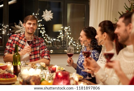 holidays and celebration concept - happy friends with glasses of wine having christmas dinner and speaking toast at home #1181897806