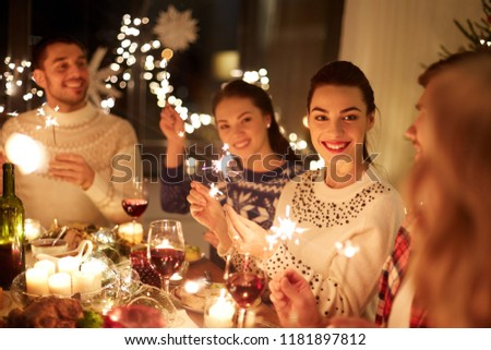 winter holidays and people concept - happy friends with sparklers celebrating christmas at home feast #1181897812