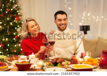 christmas, holidays, technology and people concept - happy couple in taking selfie by smartphone at home dinner