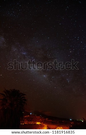 Milky Way over La Pama with palm tree with orange street lights