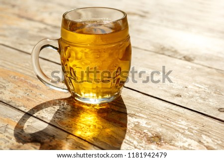 Light beer mug illuminated by the sun on a wooden table outdoors #1181942479