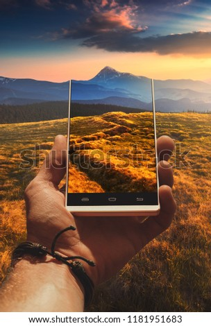 Mountain valley at sunset light on a screen of smartphone taking by man hand. Travel and adventure concept.