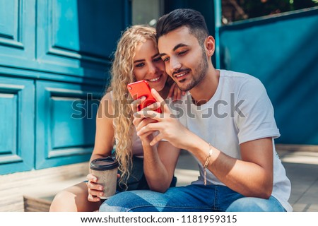 Mixed race couple in love walking in city. Arab man and white woman drinking coffee and using smartphone outdoors #1181959315