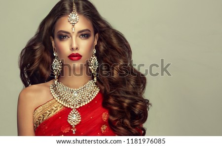 Portrait of beautiful indian girl. Young hindu woman model with kundan jewelry set. Traditional India costume red sari #1181976085