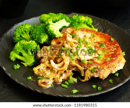 Fried pork steak with broccoli and onion sauce. #1181980315