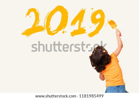 Cute little girl drawing new year 2019 with painting brush on wall background Royalty-Free Stock Photo #1181985499
