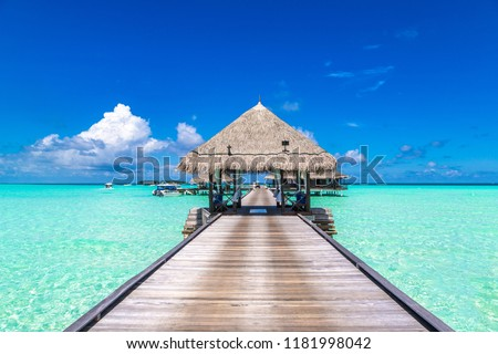 MALDIVES - JUNE 24, 2018: Water Villas (Bungalows) and wooden bridge at Tropical beach in the Maldives at summer evening #1181998042