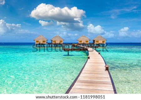MALDIVES - JUNE 24, 2018: Water Villas (Bungalows) and wooden bridge at Tropical beach in the Maldives at summer day #1181998051