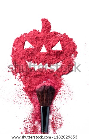 Abstract explosion Halloween shining pumpkin silhouette with cosmetic powder with make up brush isolated on white background creative concept