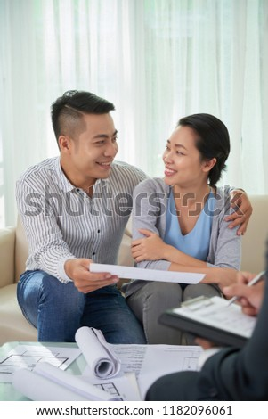 Cheerful young Asian couple meeting with estate agent and discussing documents #1182096061