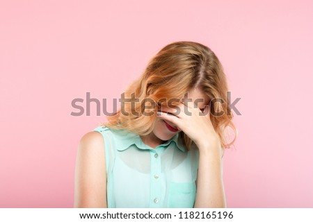facepalm embarrassment and shame emotion. ashamed smiling girl covering her face with a hand. young beautiful woman portrait on pink background. #1182165196