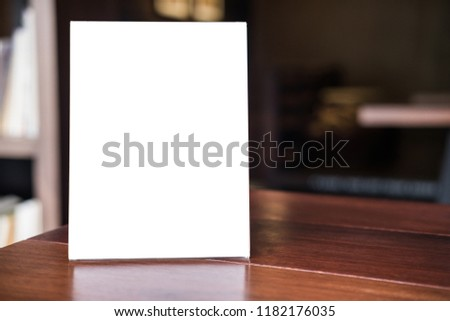 Mock up blank menu frame on table in coffee shop stand for your text of display your product.