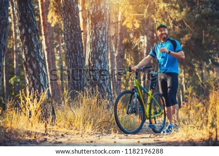 Happy bearded man cyclist rides in the sunny forest on a mountain bike. Adventure travel. #1182196288