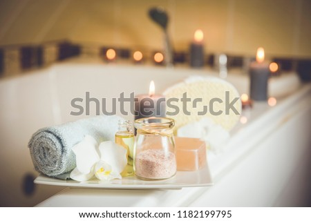 White ceramic tray with home spa supplies in home bathroom for relaxing rituals. Candlelight, salt soap bar, bath salt in jar, massage, bath oil in bottle, blue rolled towel, natural sponge.  #1182199795