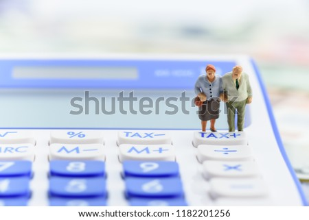 Retirement / pension income tax and social security benefit concept : Older american couple stands near a tax button on a calculator, depicts a single largest expense in retirement e.g pension tax #1182201256