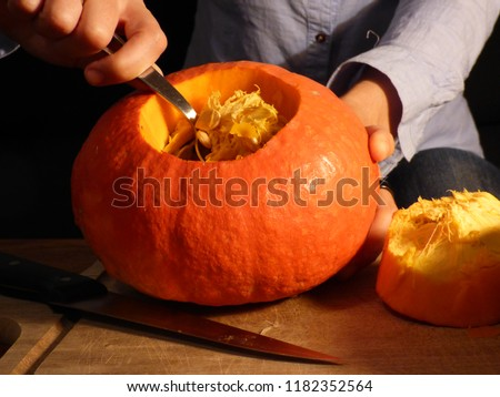 Hollowing out a pumpkin for Halloween party, Jack o lantern in progress, Autumn celebration. Cooking Thanksgiving dinner for family gathering, delicious pumpking soup or pie in preparation. #1182352564