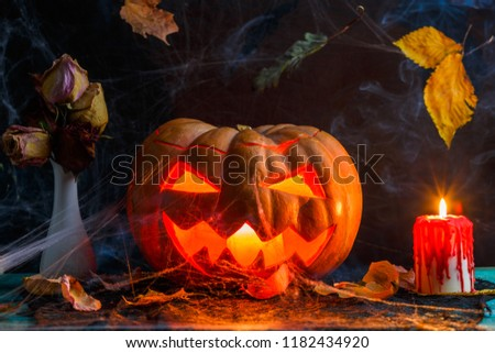 Halloween photo of table with pumpkin, burning candle, cobweb