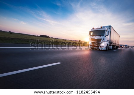 Loaded European truck on motorway in beautiful sunset light. On the road transportation and cargo. #1182455494