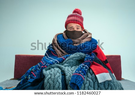 Bearded sick man with flue sitting on sofa at home or studio covered with knitted warm clothes. Illness, influenza, pain concept. Relaxation at Home. Healthcare Concepts. Royalty-Free Stock Photo #1182460027