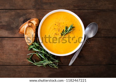 Pumpkin and carrot  Cream soup on  wood rustic  background. Autumn cream-soup in country style. Top view. Copy space #1182467221