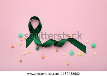 Green ribbon with colorful pills. Medical concept #1182468682