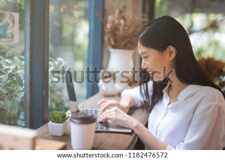 Happy young Asian girl working at a coffee shop with a laptop #1182476572