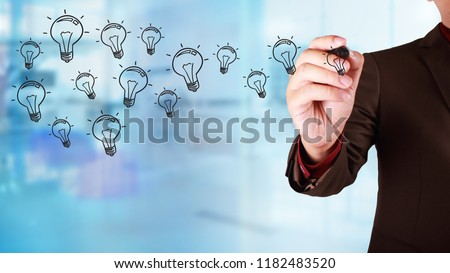Business concept. Businessman draw on virtual screen with idea light bulb icons flying over. Against blur blueish background #1182483520
