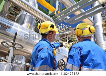 group of industrial workers in a refinery - oil processing equipment and machinery  #1182497122