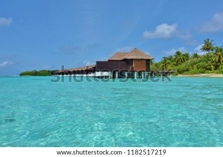 NORTH MALE, MALDIVES -6 JUL 2018- View of expensive luxury over the water bungalows with thatched roofs at the Sheraton Maldives Full Moon Resort & Spa hotel on Furanafushi Island, North Malé Atol.  #1182517219
