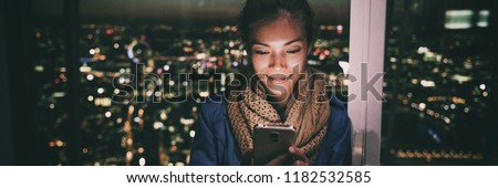 Woman texting instant messaging text on mobile phone online at night - bright light from screen illuminating young Asian girl in London city background banner panorama. #1182532585