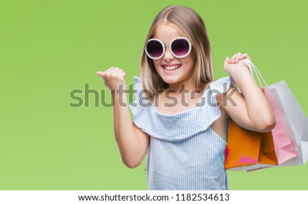 Young beautiful girl holding shopping bags on sales over isolated background screaming proud and celebrating victory and success very excited, cheering emotion #1182534613