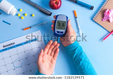 The diabetic measures the level of glucose in the blood. World Diabetes day, 14 November. Diabetes concept. Diabetic supplies on a blue background. #1182539971