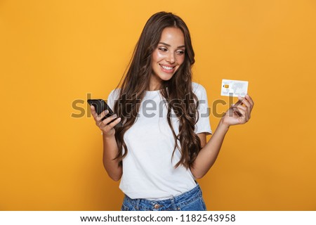 Portrait of a joyful young girl with long brunette hair standing over yellow background, holding mobile phone, showing plastic credit card #1182543958