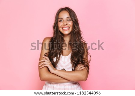 Image of european lovely woman 20s with long hair wearing dress smiling at you with arms crossed isolated over pink background