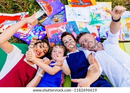 Smiling creative family paitners of mother, father, and two children in aprons lying down on grass with drawings outside having fun with thumbs up outstrectched to the camera. #1182696619