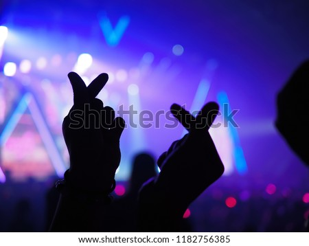 K-Pop music theme or Live concert background with silhouette hands of audience making mini heart shaped hand gesture for artist supporting on blurred background of audience and stage with neon light. Royalty-Free Stock Photo #1182756385