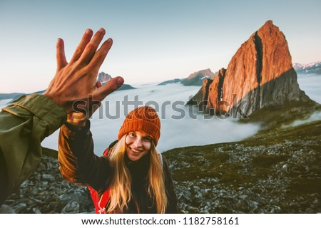 Couple friends giving five hands traveling outdoor hiking in Norway mountains adventure lifestyle positive emotions concept family together on journey vacations #1182758161