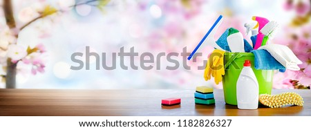 Bucket or basket with cleaning items on wooden table and blurry pink flowers tree background. Washing set with copy space banner. #1182826327