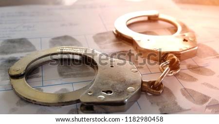 Crime and violence concept.Police Handcuffs on fingerprints crime page file #1182980458