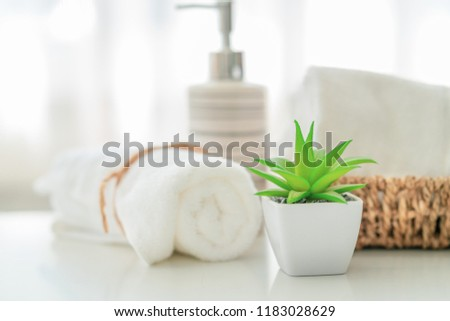 Ceramic soap, shampoo bottles and white cotton towels on white counter table inside a bright bathroom background #1183028629