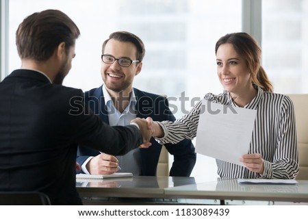 Happy employers shake hand of male job candidate, congratulating with given position, satisfied HR managers happy to hire applicant handshake greeting at team. Successful good interview concept #1183089439