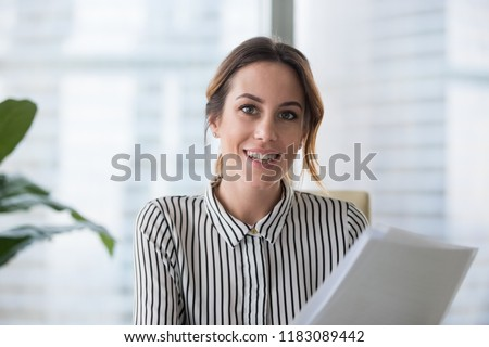 Portrait of smiling millennial businesswoman holding documents looking at camera, headshot of happy woman worker or female ceo posing with paperwork making picture at corporate close up photoshoot. #1183089442