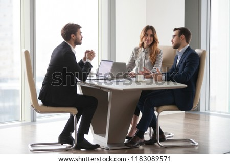 Diverse business partners busy discussing new corporate project coworking during meeting, colleagues negotiate considering startups, analyzing company statistics during briefing. Cooperation concept #1183089571