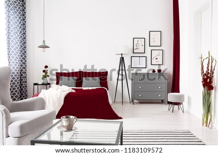 Glamour bedroom interior in white, gray and burgundy with a bed dressed in wine color linen. Lamp and drawer cabinet by the bed. Real photo. #1183109572