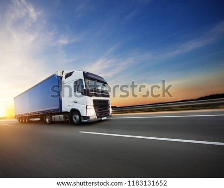 Loaded European truck on motorway in beautiful sunset light. On the road transportation and cargo. #1183131652
