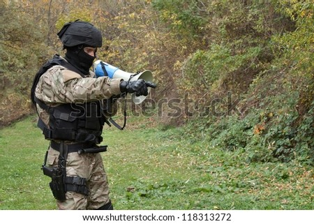 A policeman shouts orders into a megaphone #118313272