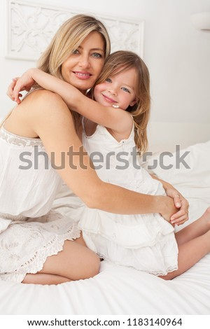 Beautiful family mother and young daughter hugging together on bed, white home interior, looking smiling. Healthy mom and child closeness, fun lifestyle. #1183140964