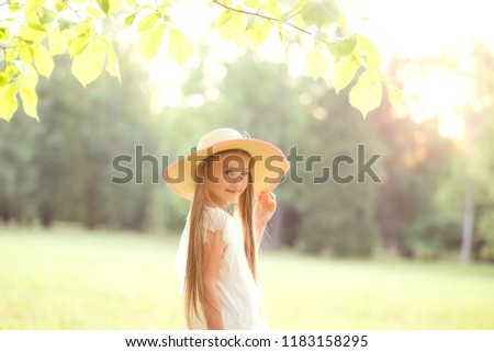 portrait of a lovely cute blonde girl with long hair in a light straw hat. close. sunny warm summer day #1183158295