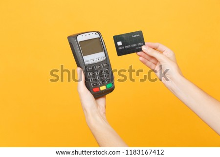 Close up cropped photo of female holding in hands wireless modern bank payment terminal to process acquire credit card payments, black card isolated on yellow background. Copy space for advertising #1183167412